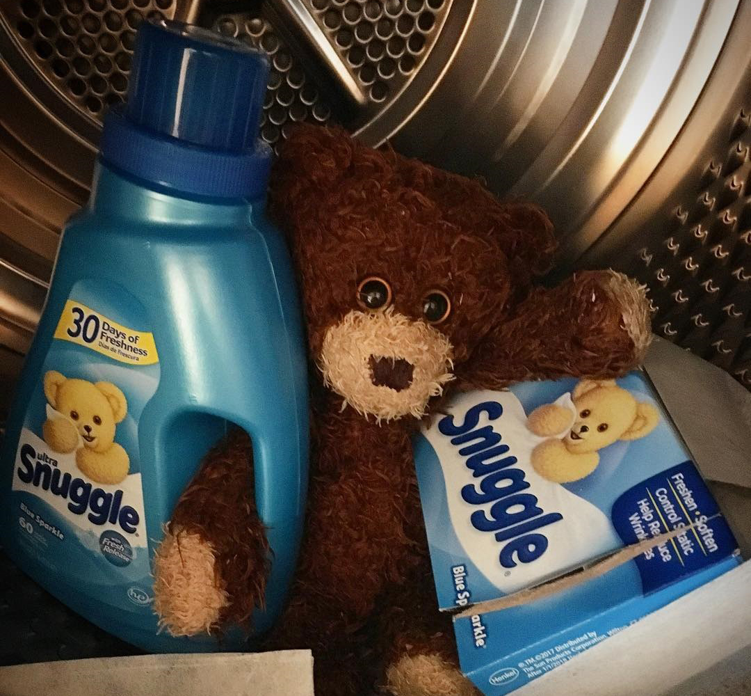 fabric softener getting held by a cute stuffed animal inside of a dryer