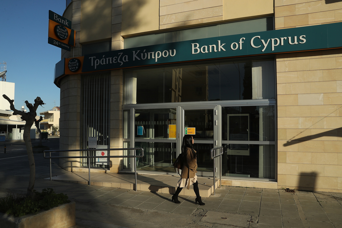A woman walks past a local branch of Bank of Cyprus on March 5, 2017 in Nicosia, Cyprus.