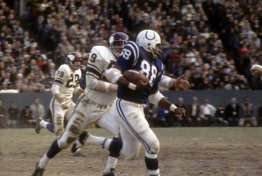 BALTIMORE, MD - CIRCA 1965:  John Mackey #88 of the Baltimore Colts runs away from Lonnie Warwick #59 of the Minnesota Vikings during an NFL football game at Memorial Stadium circa 1965 in Baltimore, Maryland. Mackey played for the Colts from 1963-71.