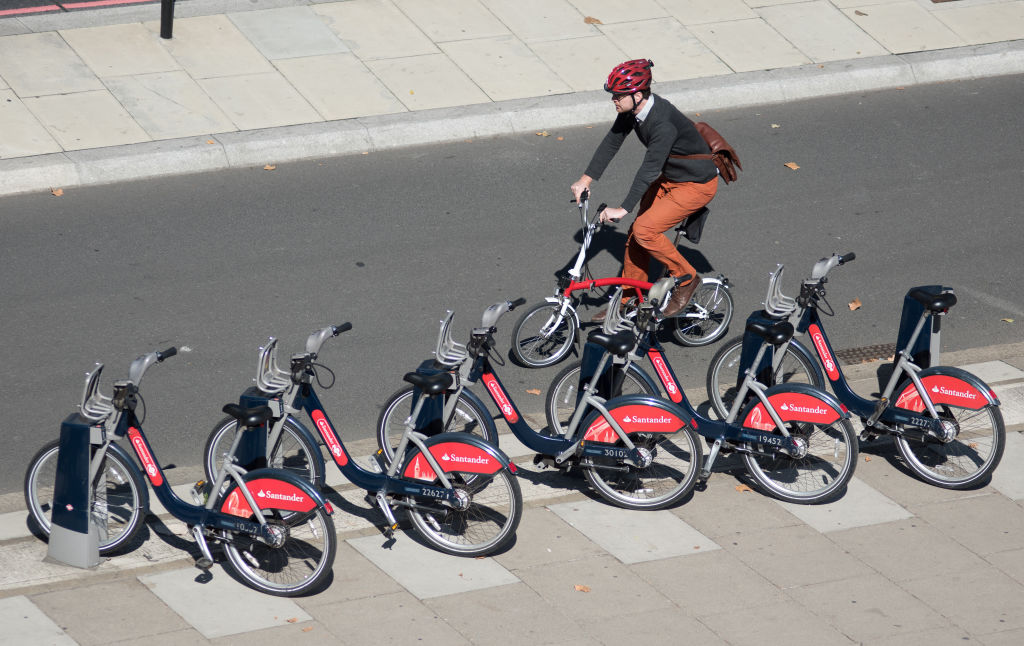 A cyclist passes by a docking station of Santander bicycles