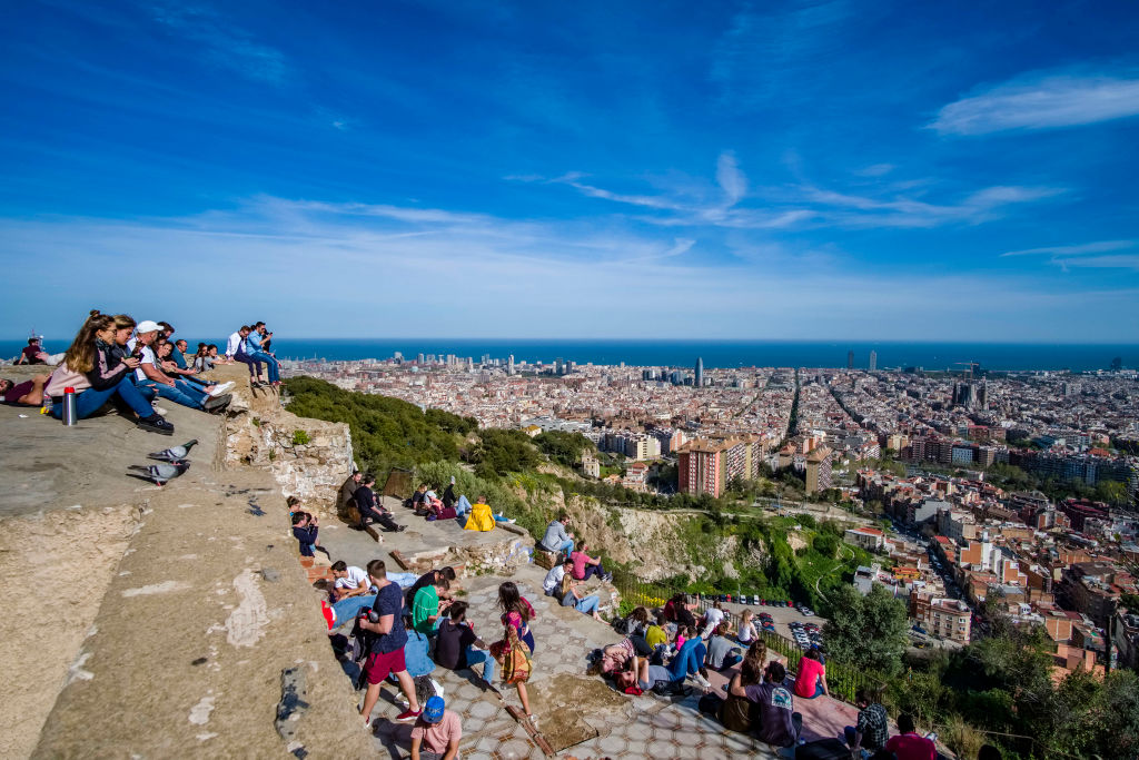 People gather on steps to overlook the aerial view of Barcelona