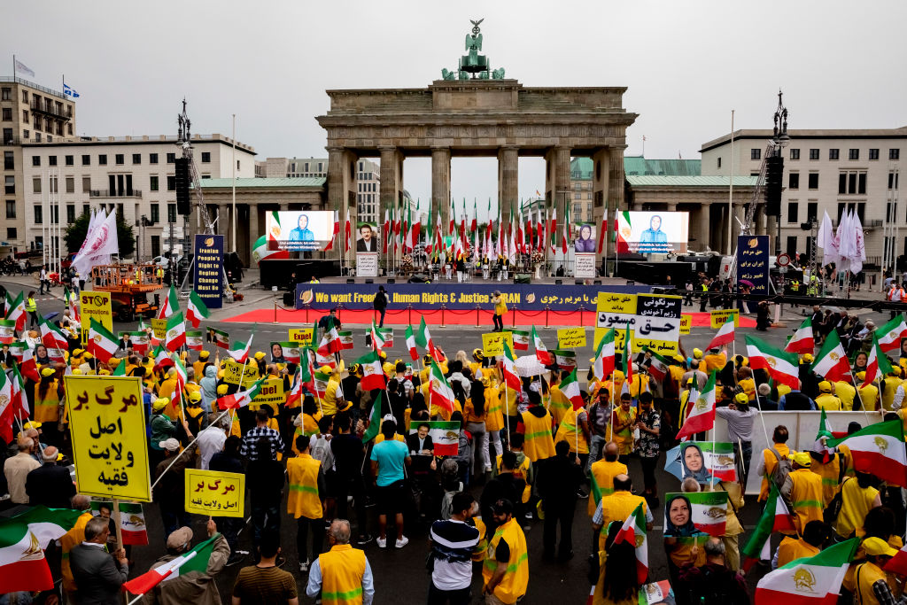 Ralliers gather before the Brandenburg Gate wearing the colors of Iran