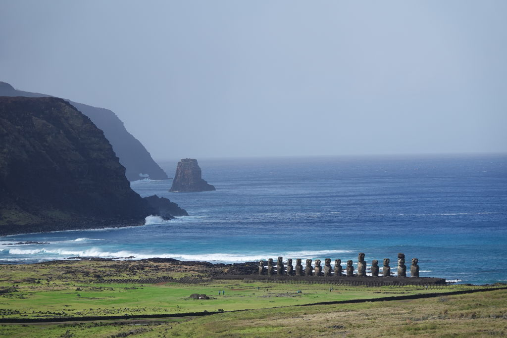 Tourists are barely visible compared to the giant statues of Eastern Island in this faraway photo