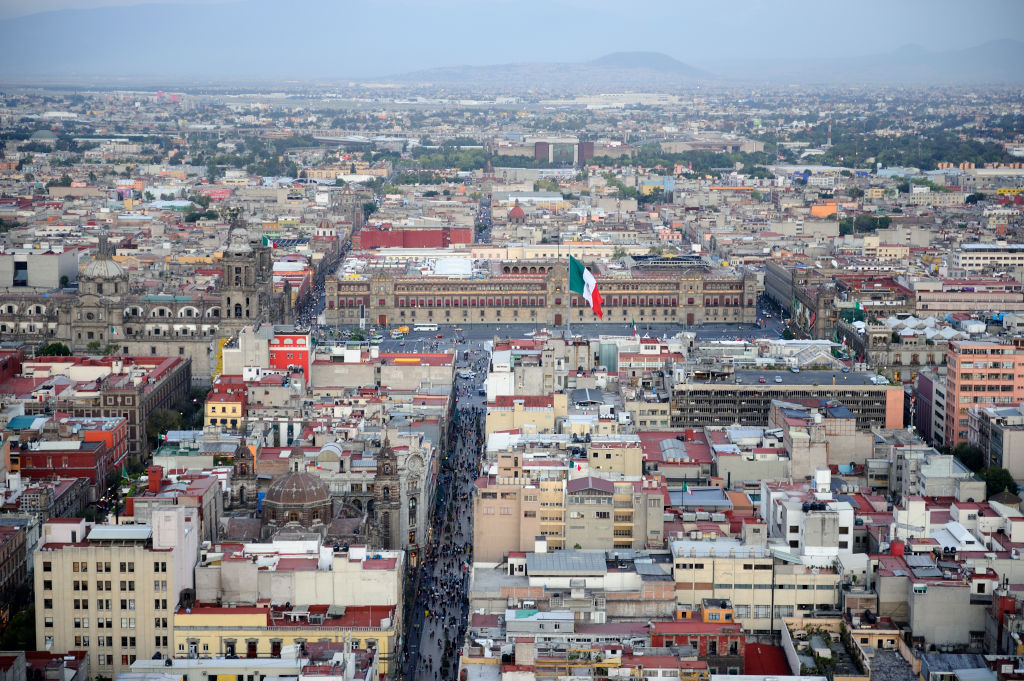 An aerial view of Mexico City shows buildings and a Mexican flag blowing in the wind