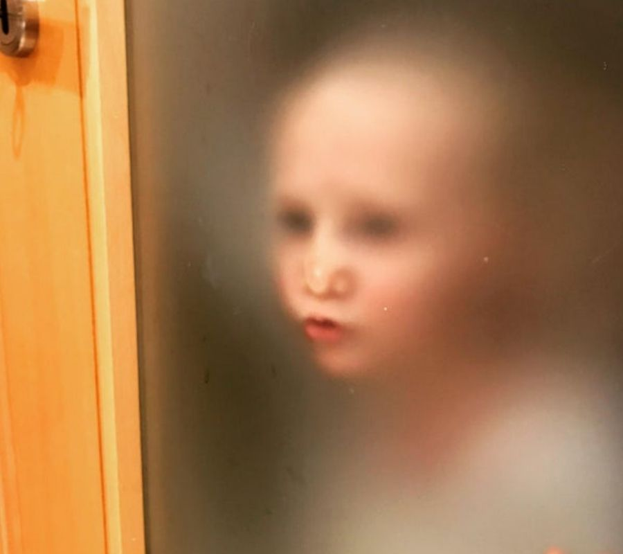 kid puts face against fogged up see through bathroom door