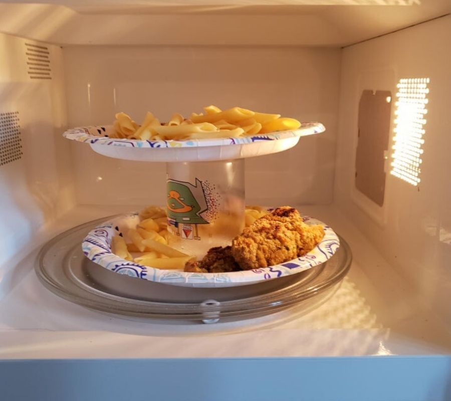 plates stacked on top of a cup to make room in a microwave