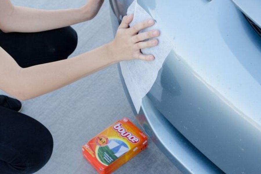 woman polishing chrome bumper with dryer sheet