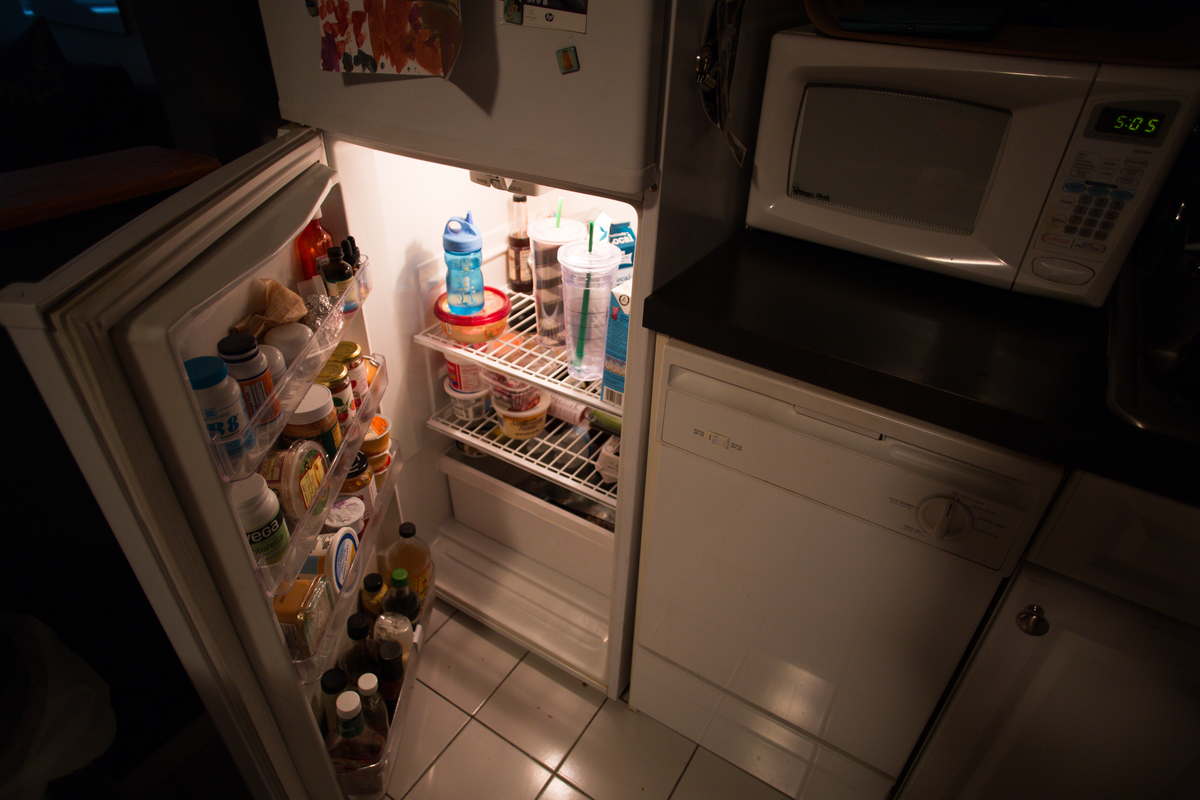 A refrigerator is open at night.