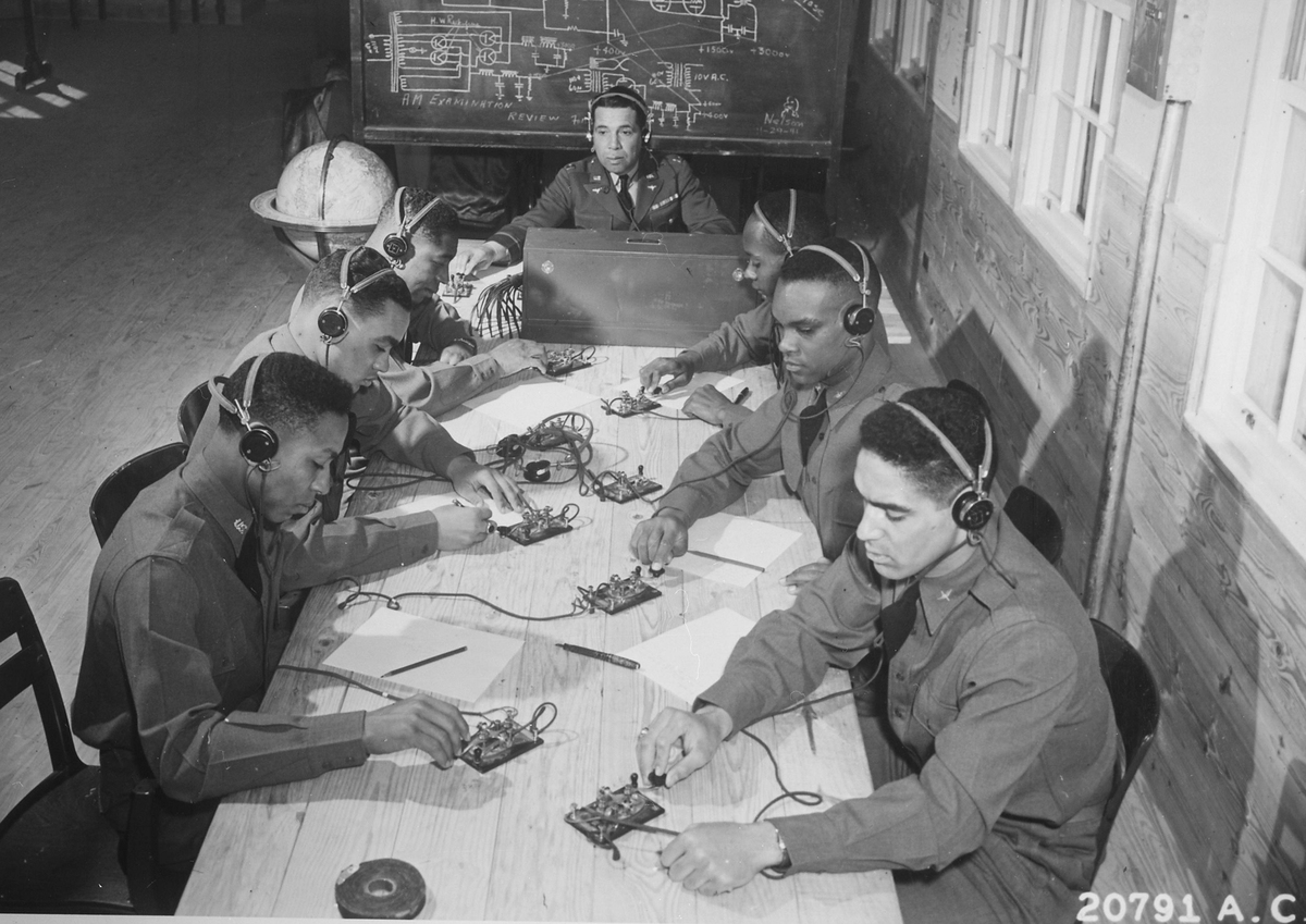 A captain in the Air Corps (center) teaches cadets how to send and receive code during flying school.