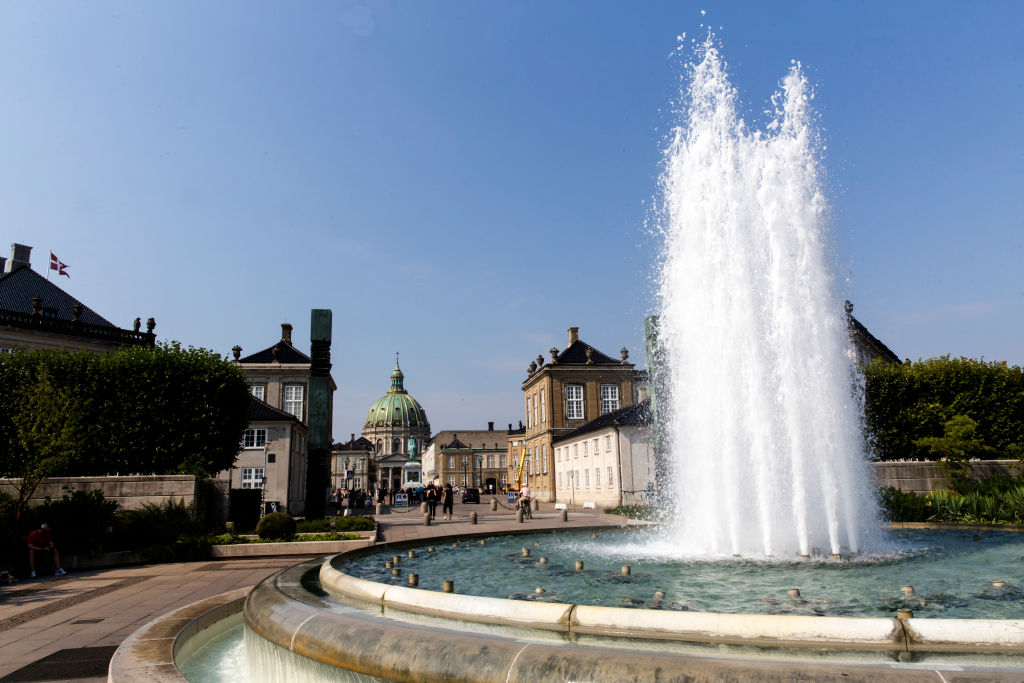 A fountain sits at the mouth of a town square in Denmark.