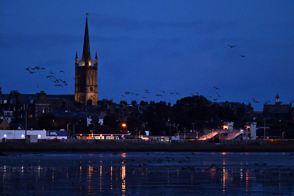 Geese fly past a builing in Scotland at night.