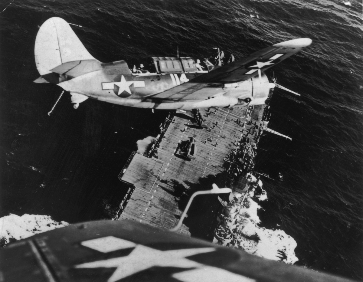 A US Navy Curtiss Helldiver (SB2C) prepares for a landing on an aircraft carrier after a bombing mission against a Japanese warship.