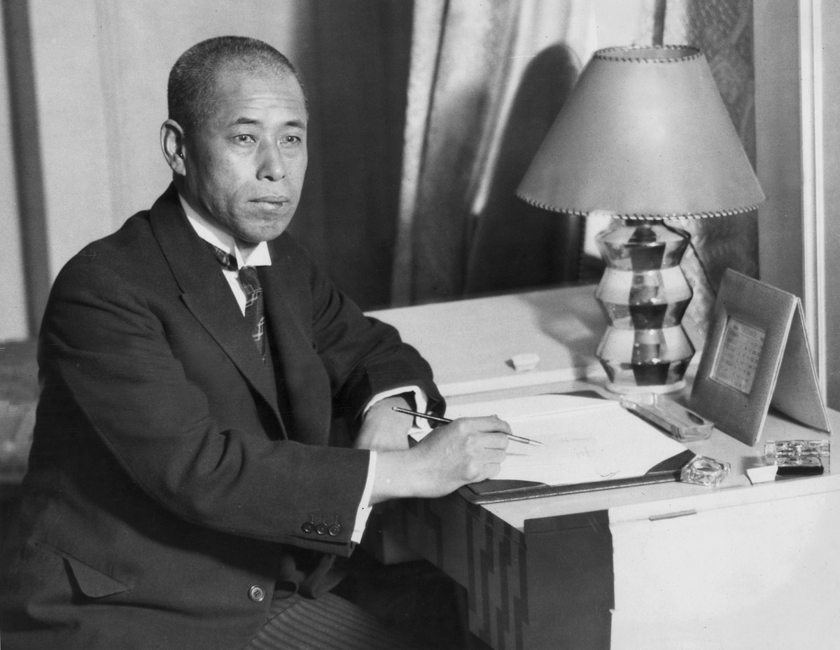 Portrait of Japanese admiral Isoroku Yamamoto, wearing a suit and tie, seated at a desk with a pen in his hand
