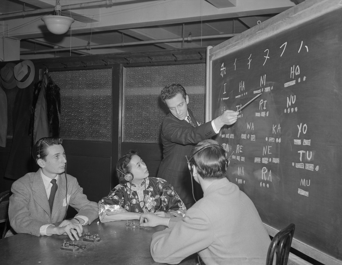 Frank Melville, Jr., points out Japanese characters to students at his Melville Aeronautical Radio School, the first school in the nation to offer a course in Jap code deciphering.