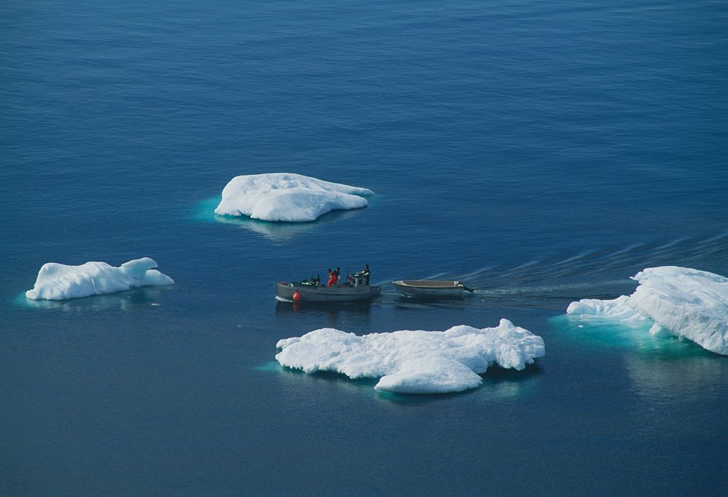 Boats with fishermen among the icebergs in Disko bay