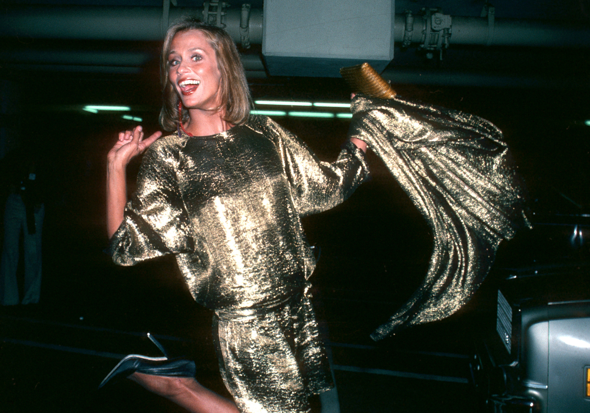 Lauren Hutton waves around a gold metallic coat in a parking lot.