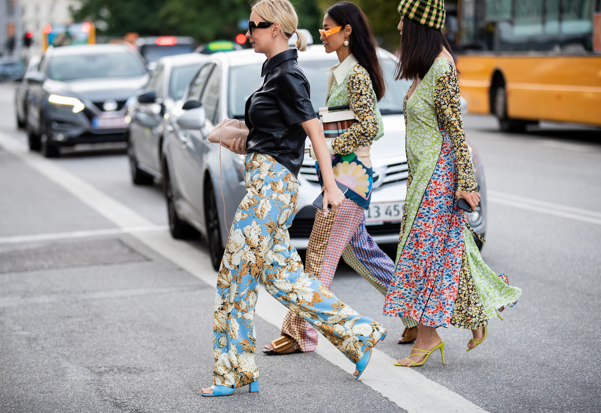 Guests of Copenhagen Fashion Week cross the street in clothes with mismatched patterns.