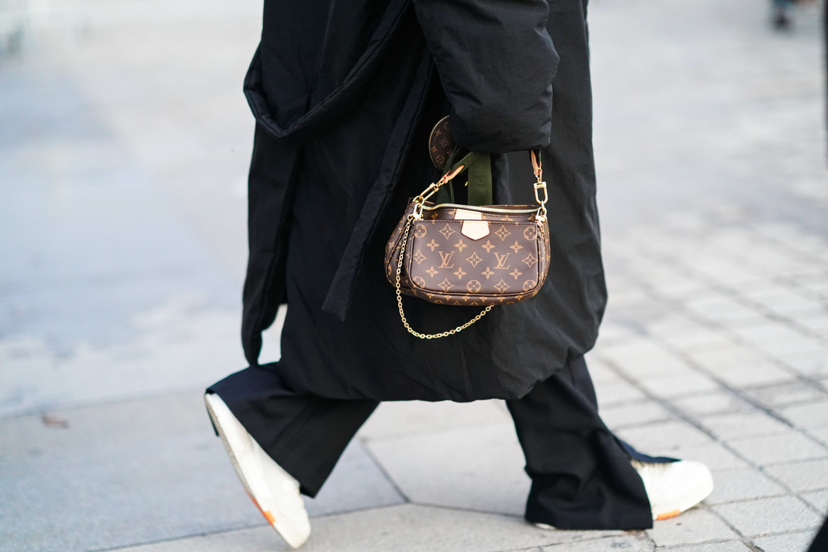A person wearing an oversized coat carries a small Louis Vuitton bag.