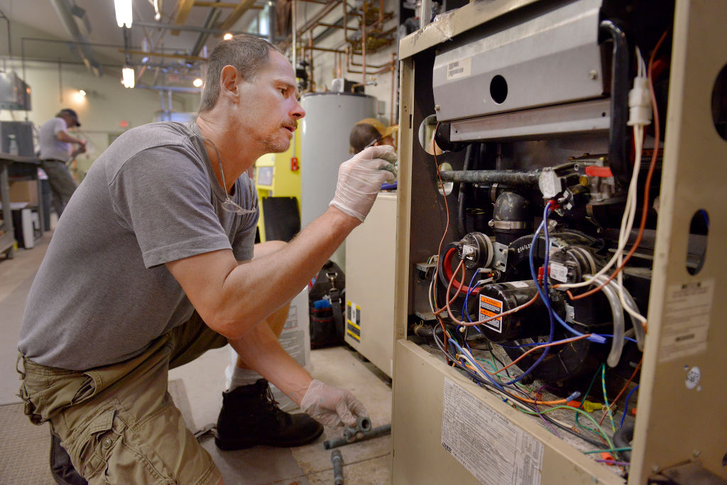 Steven Sweet, from Windham, works on a gas furnace