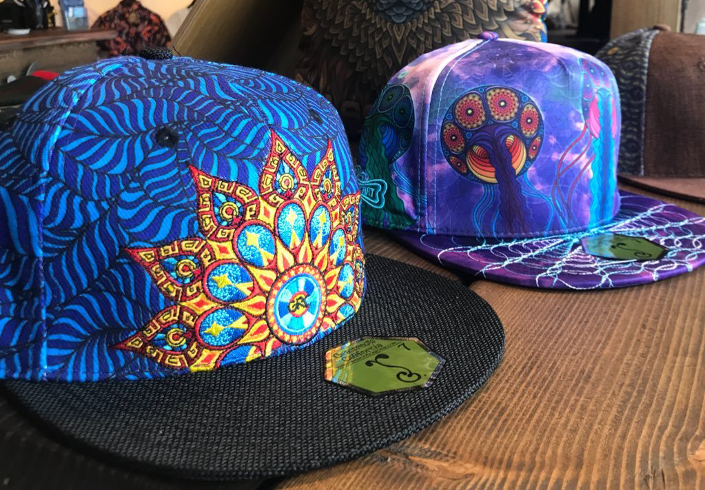 Two trucker hats have colorful designs on them.