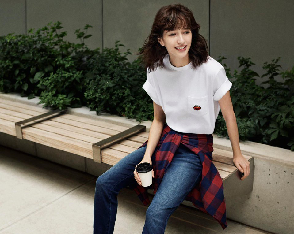 A woman with a flannel tied around her waist drinks coffee on a bench.