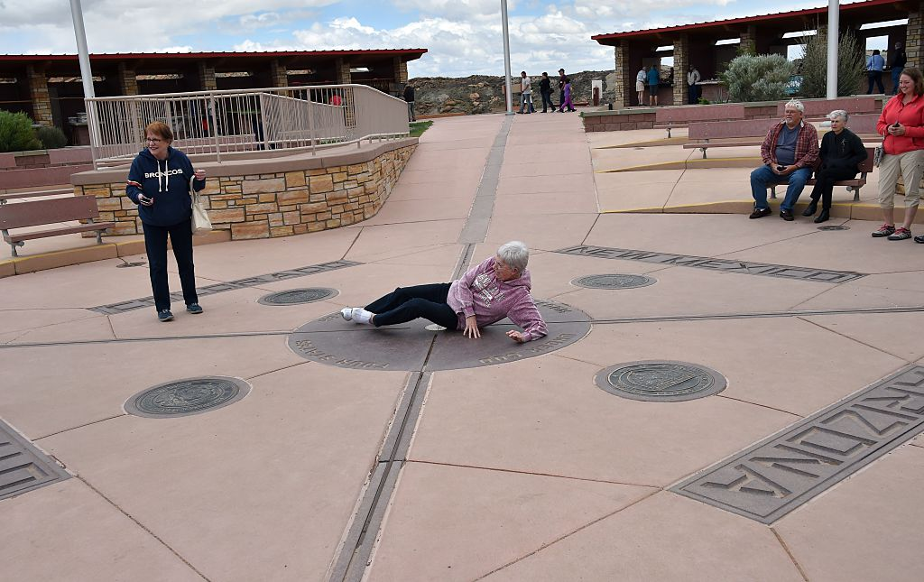 an old lady laying down on the ground of the four corners monument