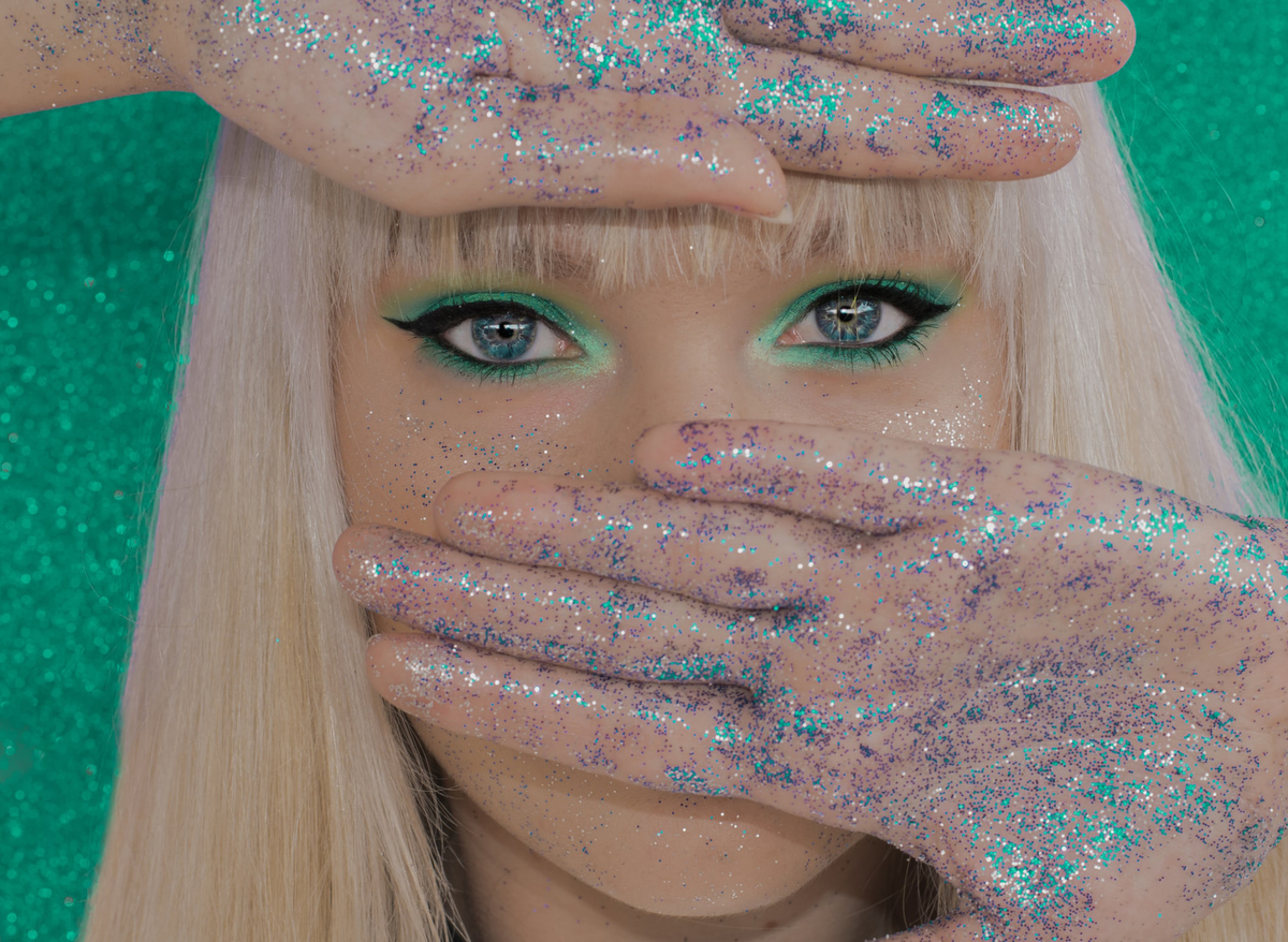 A woman has blue and purple glitter all over her hands and face.