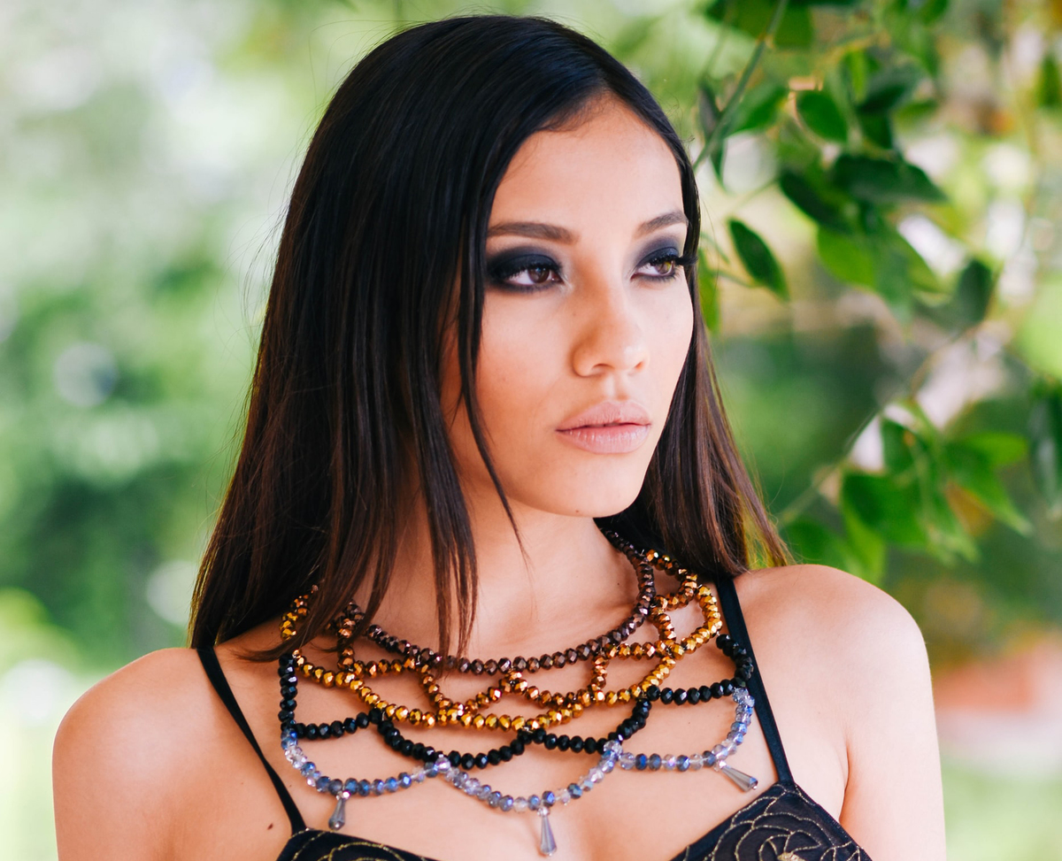 A model wears a large, elaborate beaded necklace.