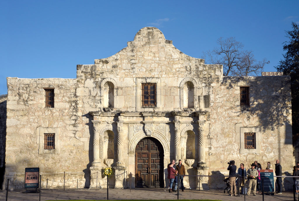 tourists posing for photos outside the alamo