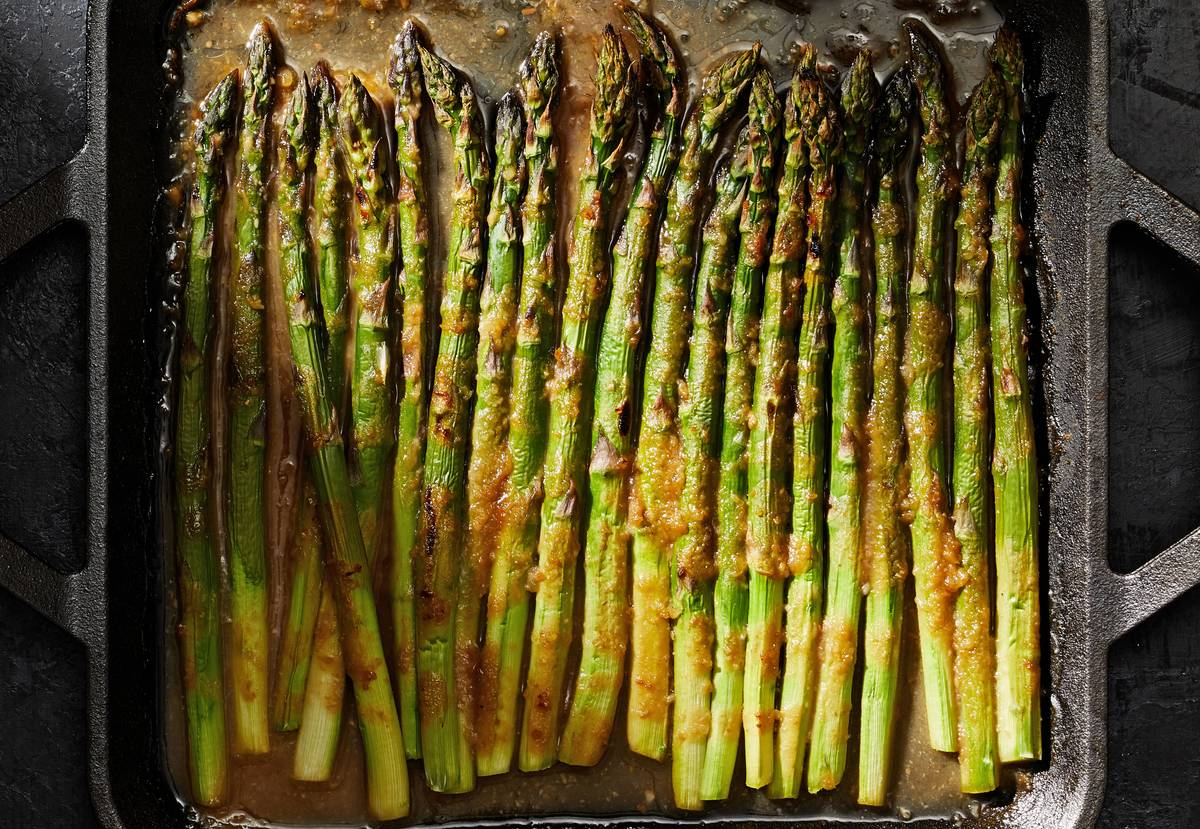 A pan of asparagus cooks in oil.