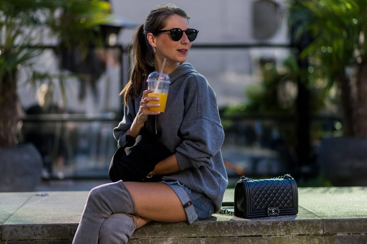 A woman drinks orange juice outside.