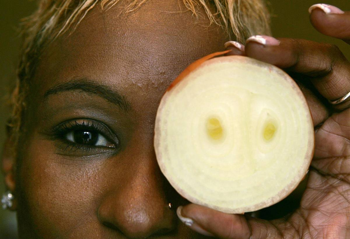 A woman holds up a white onion in front of her eye.