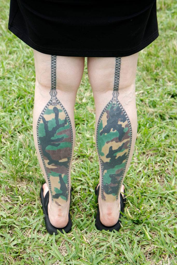 A zipper, camouflage tattoo on the back of someone's legs