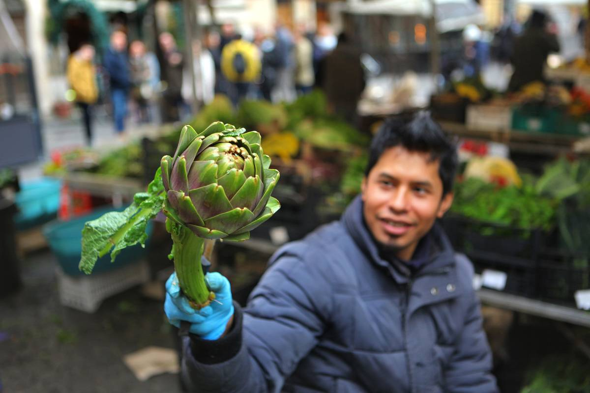 A man holds an artichoke at a market.
