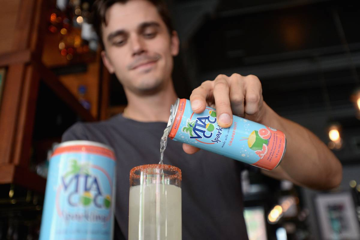 A man pours a sparkling drink with grapefruit and carbonated coconut water into a glass.