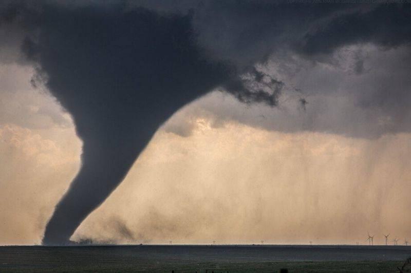 a tornado next to wind turbines