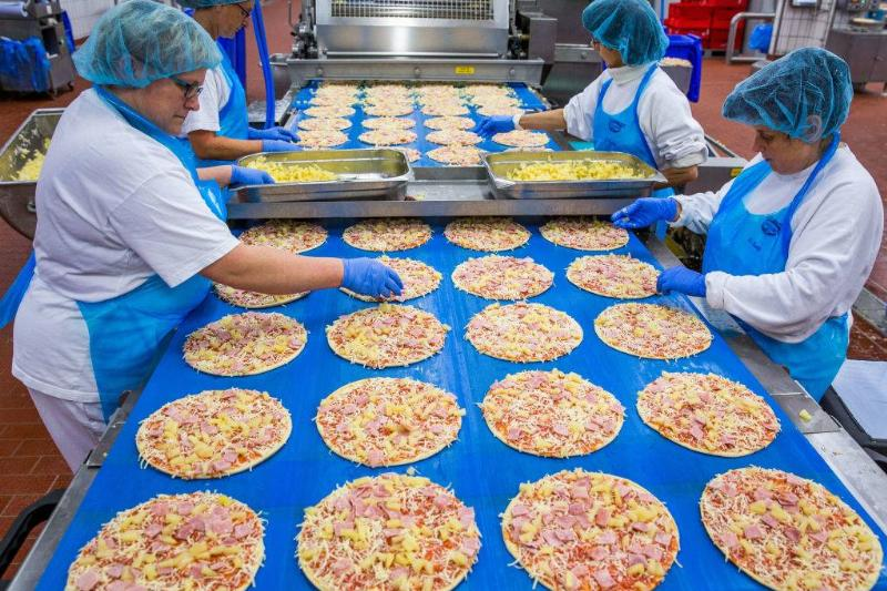 Employees add pineapple pieces to frozen pizzas on a production line