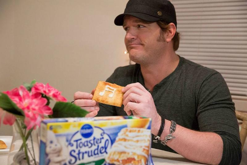 Jerrod Niemann holding up a piece of toaster strudel with a music note written in icing