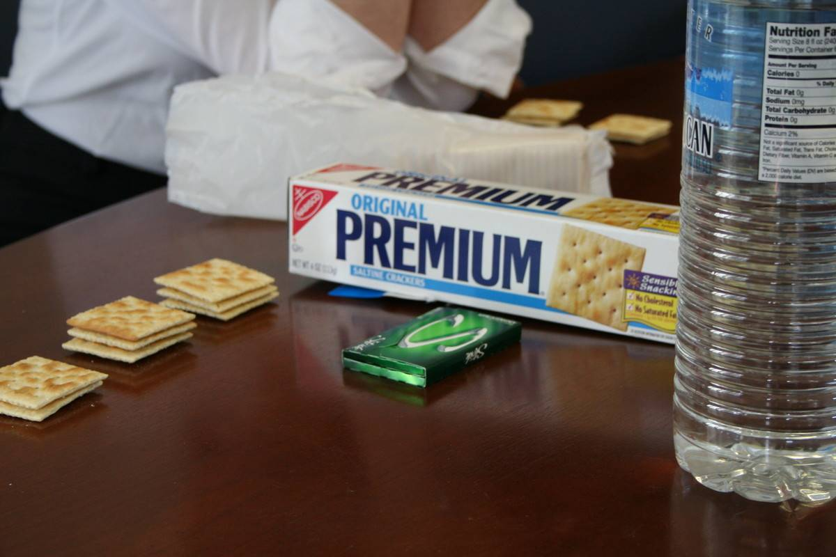 Saltine crackers lie on a table with the box nearby.
