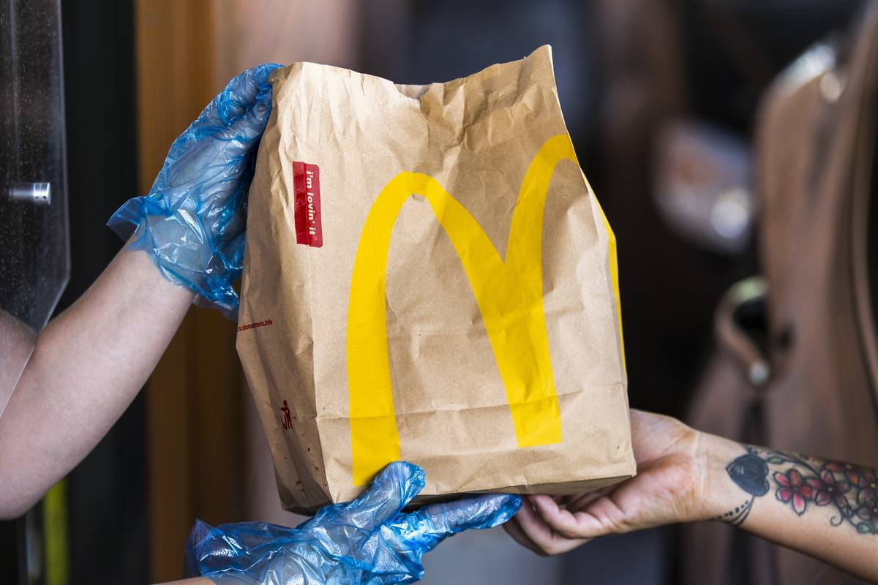 A McDonald's employee hands a customer a to-go bag through the drive-thru.