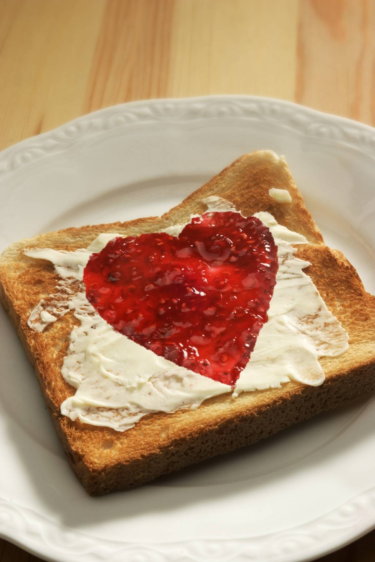 Toast is topped with butter and jelly shaped like a heart.