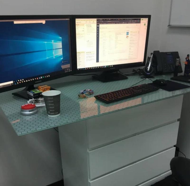 dresser with glass sheet on top with two monitors on it