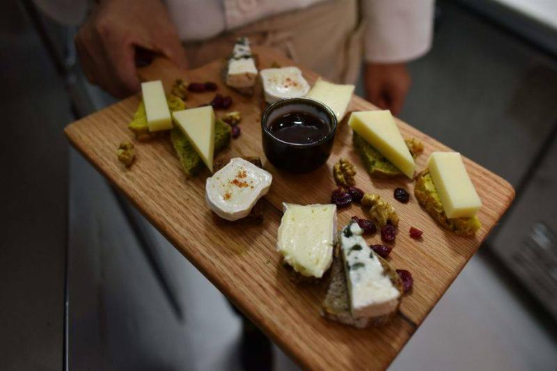 a chef displays a cheese platter featuring French brie