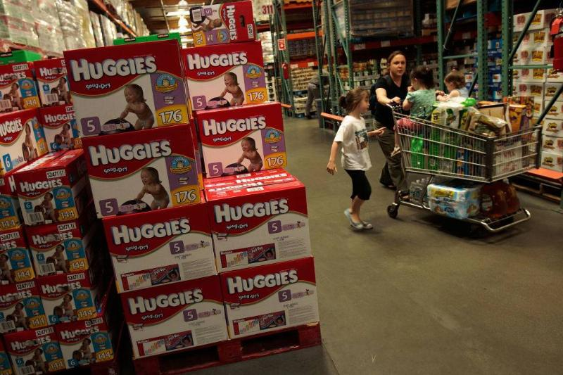A family passes by bulk packages of diapers at a Costco store