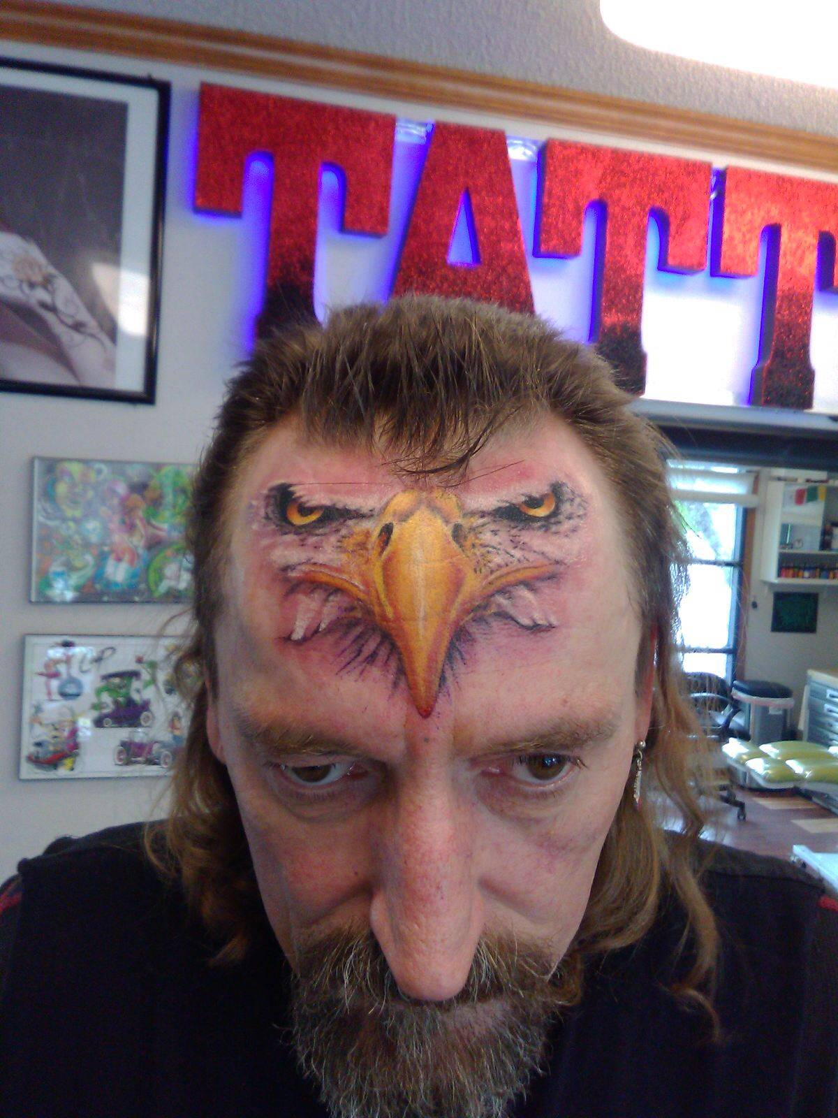 tattoo of eagle face on a man's forehead