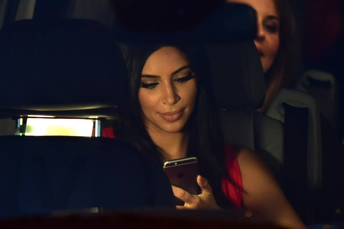 kim kardashian looking at phone sitting in car