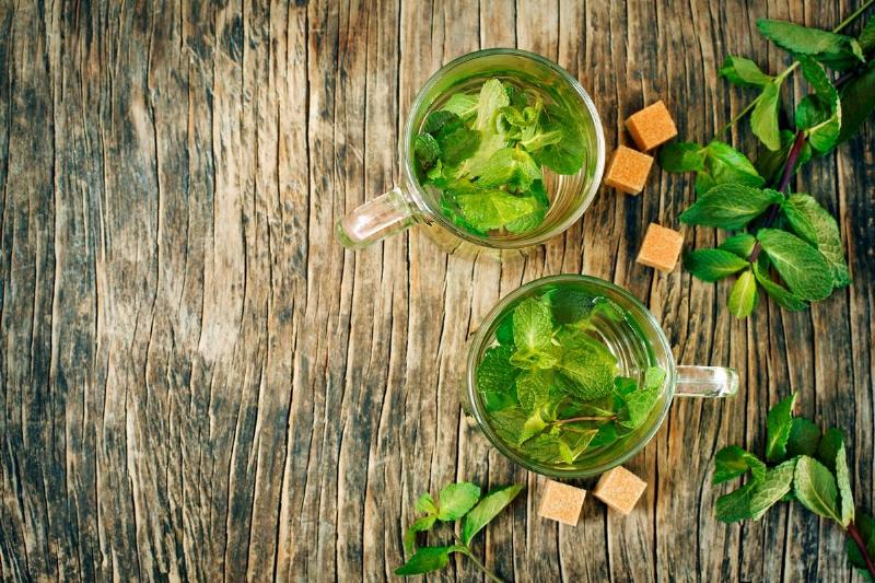 Mint tea on wooden background, top view, copy space