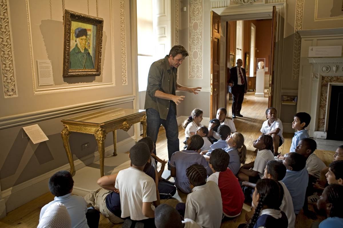 Pupils from Millfields Community School listen to storyteller Simon Parker telling a tale based on the famous painting by Vincent Van Gough, 'Self-Portrait with Bandaged Ear'.